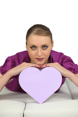 Young woman lying with heart-shaped box