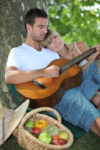 Couple with guitar in the field
