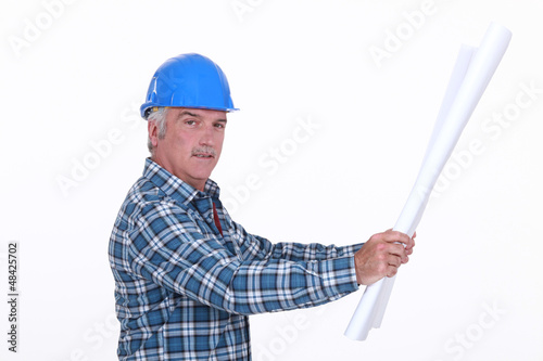 Grey haired foreman looking at plans