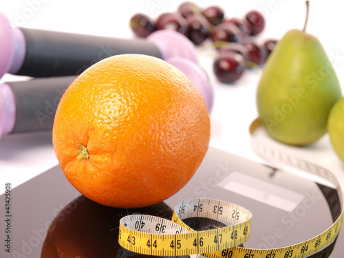 Scale with an orange fruit and a measuring tape