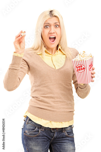 Scared blond woman holding a popcorn box and screaming