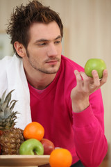 Young man picking an apple from a fruit bowl