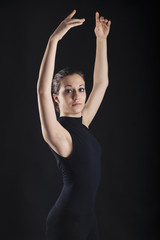 Close up portrait of young dancer isolated on black background.