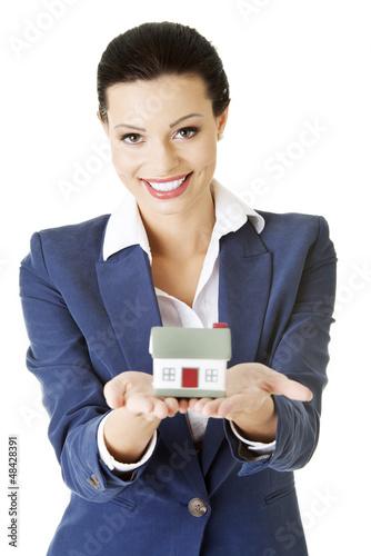 Beautiful businesswoman holding house model