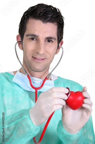 doctor auscultating plastic heart