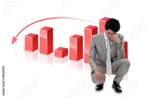 Depressed businessman in front of a bar chart