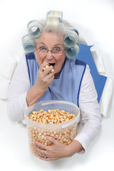 Elderly lady eating popcorn