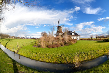 Dutch windmill by canal on green pasture