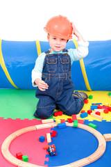 Kleiner Junge spielt Bauarbeiter mit Steinen