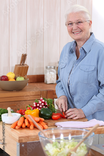 Old lady chopping vegetables