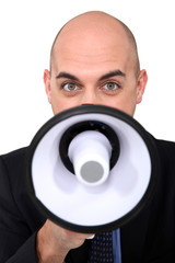 bald businessman speaking through  megaphone