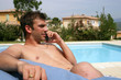 Man sat poolside with mobile phone