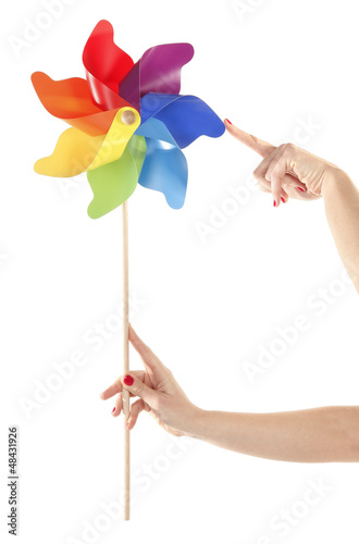 Hand are holding and moving colorful pinwheel toy