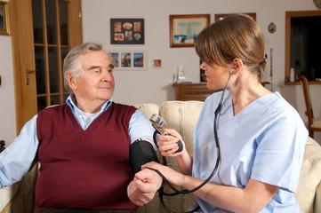 Krankenschwester nimmt Blutruck bei Senior
