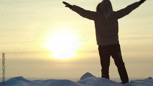 SLOW: Man poses on a summit at sunset and waves his arms