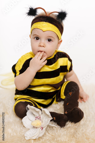 Baby wearing bee costume sitting on the floor