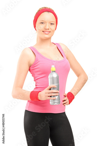 Athletic young woman in sportswear holding a bottle of water