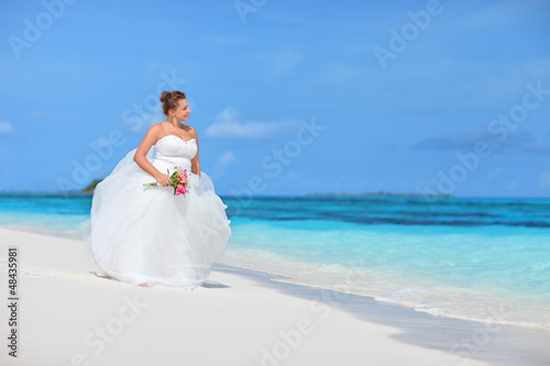 Bride watching towards the see on an exotic beach