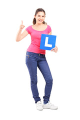 Happy teenager holding L plate and giving a thumb up