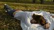 Young woman sleeping on a bedspread in the park and the autumn