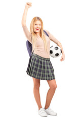 Euphoric female student with backpack holding a soccer ball