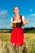Junge Frau trinkt Bier und hält Brezel