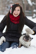 Teen girl with pug puppy in snow