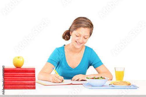 Teenage girl writing homework and having a meal