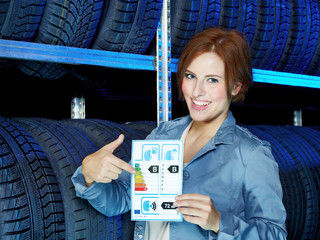 Female customer presenting EU tire labeling in a garage