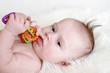 Portrait of the sad baby with a rattle (3,5 months)