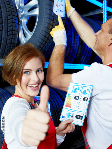 Apprentice for car mechanic shows thumb up for tire label