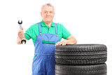 Mature mechanic standing with car tires and holding a wrench
