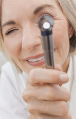 Senior Female Doctor With Otoscope or Ear Speculum