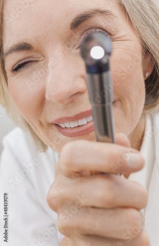 Senior Female Doctor With Otoscope or Ear Speculum