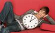 junge Frau liegt mit einer Uhr auf der Couch