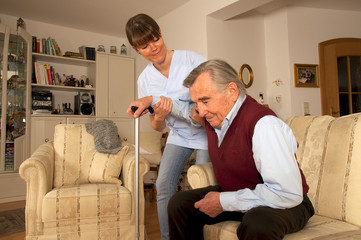Krankenpflegerin hilft Senior beim Aufstehen