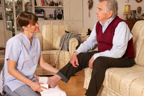 Pflegerin verbindet Fuß eines Senioren
