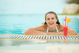 Smiling young woman relaxing in pool with cocktail