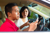 Asian man texting while driving