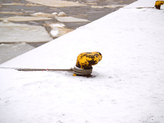 Bollard and mooring lines, covered with snow