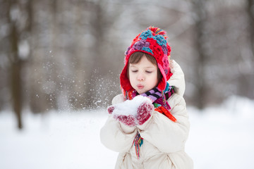 Adorable preschooler girl in beautiful winter park