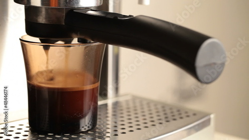 Coffee drips into a dark glass in espresso coffee machine