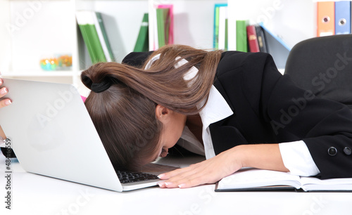 Tired business woman with notebook in her workplace