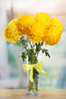 bright yellow chrysanthemums in glass vase, on wooden table