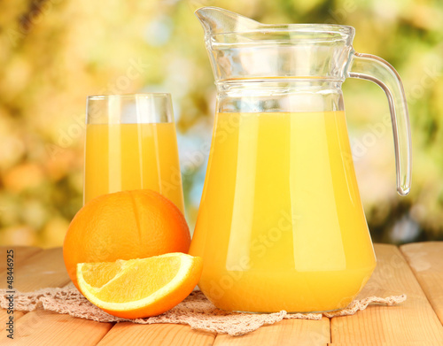 Full glass and jug of orange juice and oranges