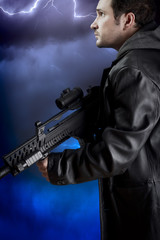 Man with long leather jacket and assault rifle over storm backgr
