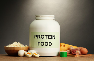 jar of protein powder and food with protein, on grey background