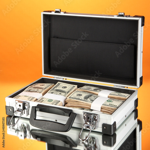 Suitcase with 100 dollar bills on orange background
