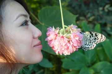 蝶々と一緒に花の香りを嗅ぐ女性