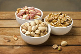 Assorted nuts in dishes on wooden table